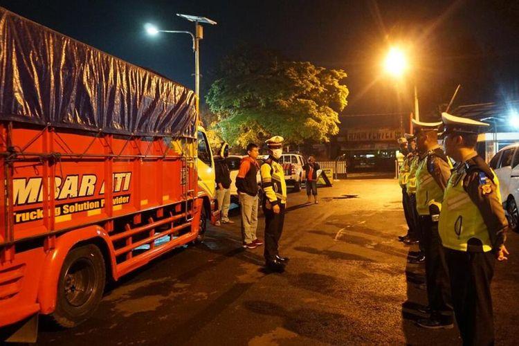 Personel Polres Cianjur, Jawa Barat, melakukan pengawalan kendaraan angkutan sembako yang akan keluar Cianjur untuk mencegah aksi bajing loncat.