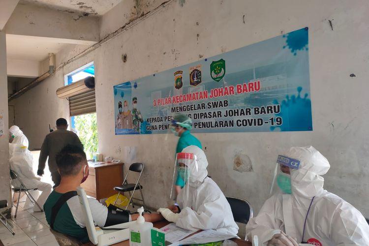 Petugas Puskesmas Kecamatan Johar Baru melakukan pemeriksaan swab kepada pedagang di Pasar Johar Baru, Jakarta Pusat, Kamis (18/6/2020)