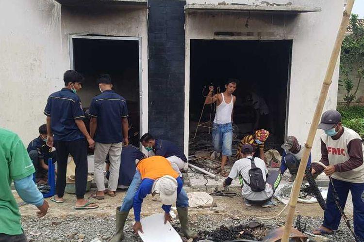 Warga Desa Beringin Kencana bergotong royong membersihkan puing-puing kebakaran di Mapolsek Candipuro, Kamis (20/5/2021).