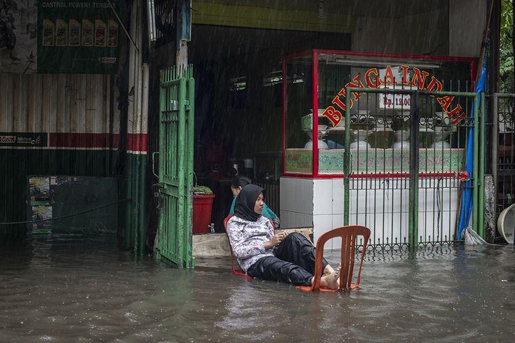 Warga duduk di depan warungnya saat banjir di kawasan Mampang Prapatan, Jakarta, Sabtu (20/2/2021). Intensitas hujan yang tinggi menyebabkan banjir di sejumlah wilayah Jakarta serta menyebabkan sebagian ruas jalan tidak dapat dilewati kendaraan.