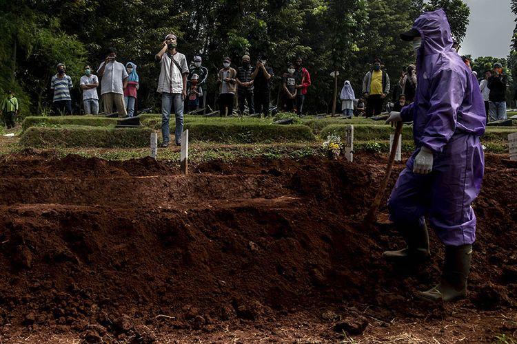 Foto dirilis Sabtu (19/9/2020), memperlihatkan petugas penggali makam menunggu kerabat jenazah korban Covid-19 mengumandangkan adzan di kompleks pemakaman Pondok Ranggon. Selain tenaga medis yang menjadi garda terdepan penanganan virus corona, salah satu pahlawan lain juga patut diberikan apresiasi tinggi adalah petugas pemakaman jenazah Covid-19.
