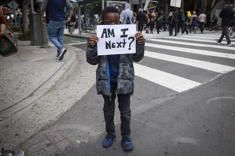 Seorang bocah lelaki kulit hitam memegang kertas bertuliskan Am I Next? yang berarti, Apakah aku selanjutnya? saat protes di pusat kota Los Angeles, Jumat, 29 Mei 2020. Protes unjuk rasa itu dipicu atas kematian George Floyd, pria kulit hitam yang meninggal di tangan polisi Minneapolis.
