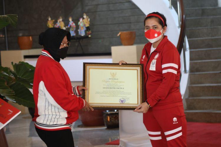 Menteri Sosial (Mensos) Tri Rismaharini memberikan piagam penghargaan kepada Leani Ratri Oktila, atlet penyandang disabilitas yang mendapatkan 2 medali emas dan 1 medali perak pada cabang olahraga para badminton Paralimpiade Tokyo 2020, Jumat (24/9/2021).