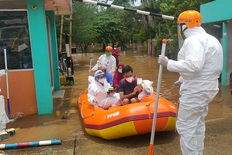 Pasien Covid-19 terdampak banjir di Perumahan Bumi Nasio Indah, Jati Asih, Bekasi dievakuasi petugas, Minggu (21/2/2021).