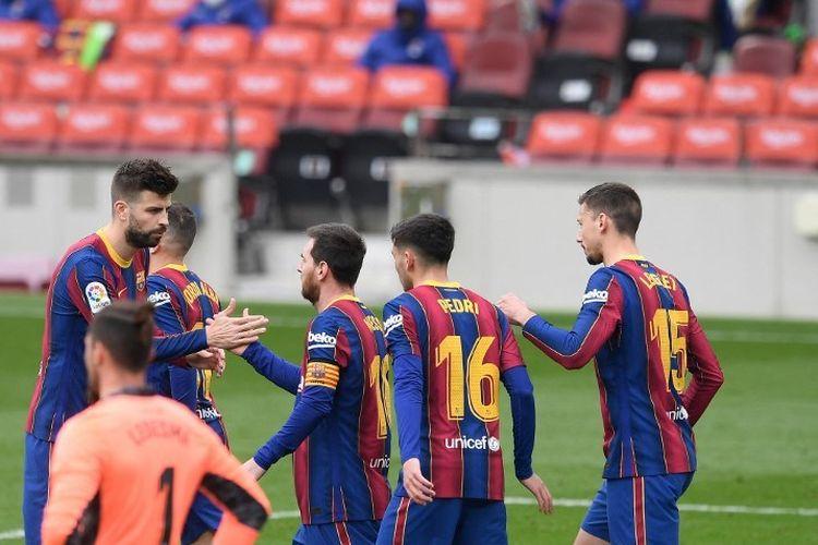 Penyerang Barcelona Barcelona Lionel Messi (tengah) merayakan dengan bek Spanyol Barcelona Gerard Pique setelah mencetak gol selama pertandingan sepak bola liga Spanyol antara FC Barcelona dan Cadiz CF di stadion Camp Nou di Barcelona pada 21 Februari 2021.
