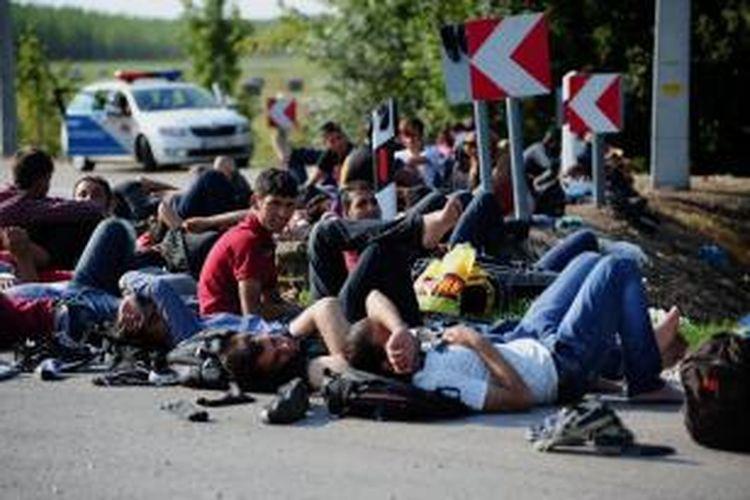 Para migran asal Timur Tengah beristirahat di jalanan dekat sebuah desa di perbatasan Hungaria-Serbia, Kamis (27/8/2015).
