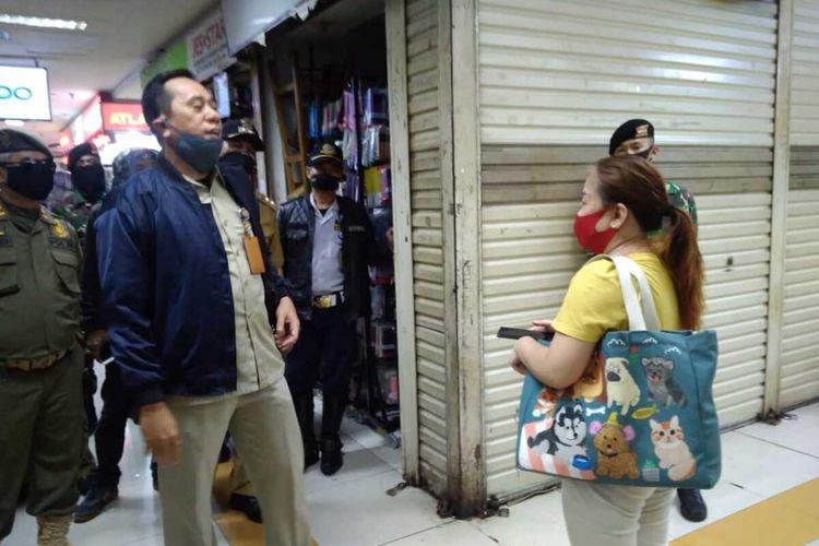 Personel gabungan Kecamatan Kramat Jati saar menutup puluhan toko di Pusar Grosir Cililitan (PGC) yang masih buka di tengah penerapan PSBB, Senin (13/4/2020).
