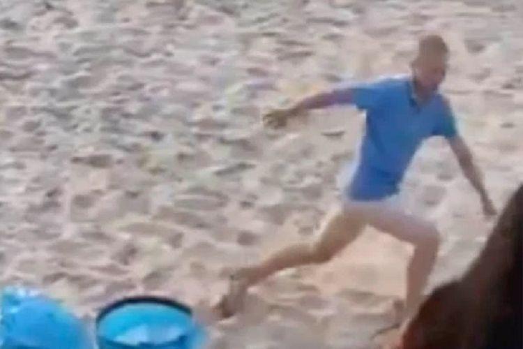 Tangkapan layar dari video yang viral di Polandia memperlihatkan seorang pria lari terbirit-birit setelah pantatnya dipukul pengunjung setempat menggunakan sandal karena dia dan pasangannya berhubungan seks di pantai.