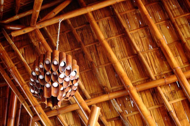 Atap gedung dibangun dari struktur bambu utuh yang menjulang.