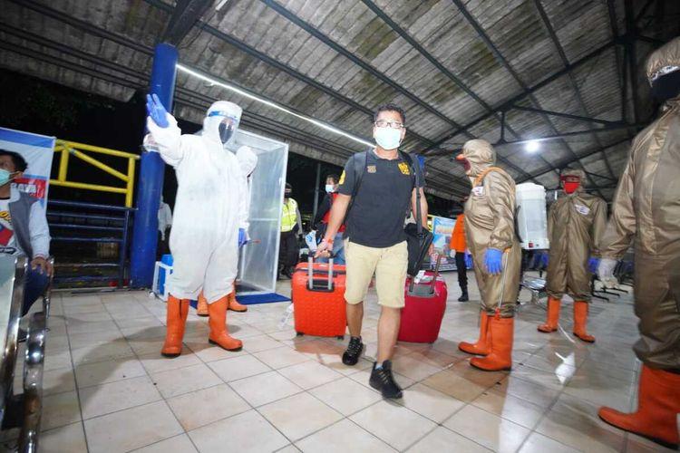 SAMBUT—Petugas Satgas Covid-19 Kota Madiun menggunakan APD lengkap menyambut kedatangan pekerja migran Indonesia yang baru pulang dari Brunei Darussalam di Terminal Purabaya Kota Madiun, Minggu (18/5/2020) malam.
