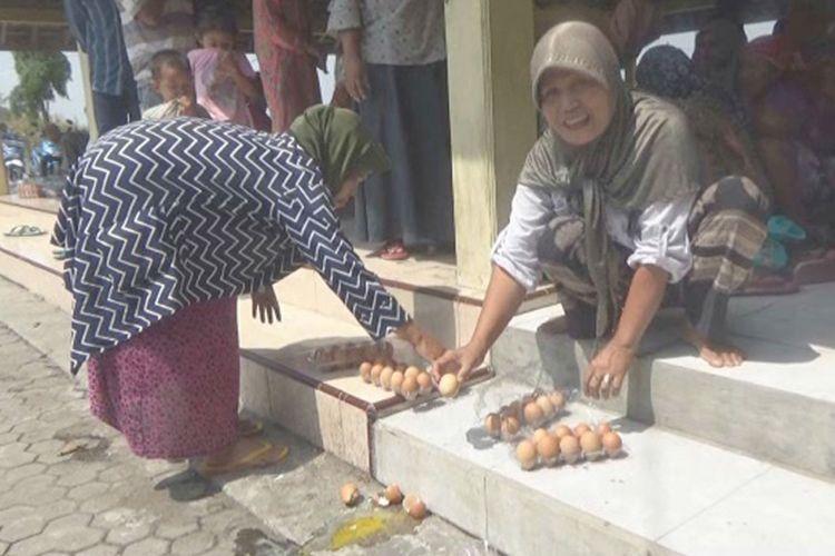 Keluarga Penerima Manfaat (KPM) program Bantuan Pangan Non-Tunai (BPNT), mengecek kualitas telur yang mereka terima di Kantor Desa Morosunggingan, Kecamatan Peterongan, Kabupaten Jombang, Minggu (25/11/2018).