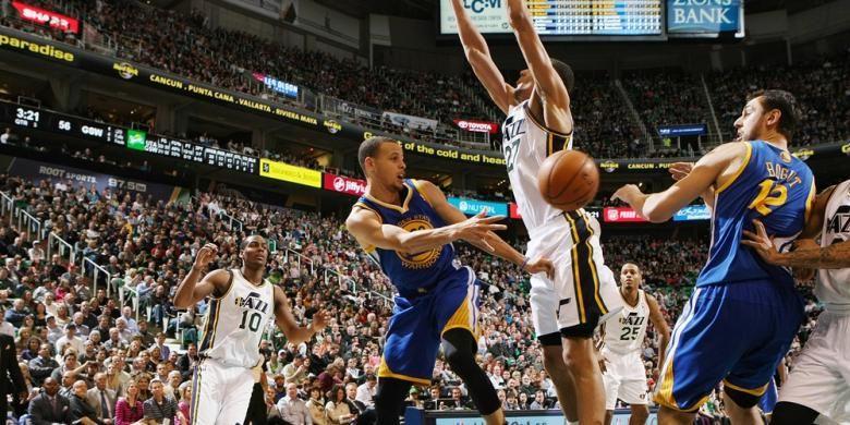 Pebasket Golden State Warriors, Stephen Curry (kiri, biru), memberikan umpan pada rekan satu timnya, Andrew Bogut (kanan, biru) pada pertandingan melawan Utah Jazz di EnergySolutions Arena, Jumat (31/01/2014).