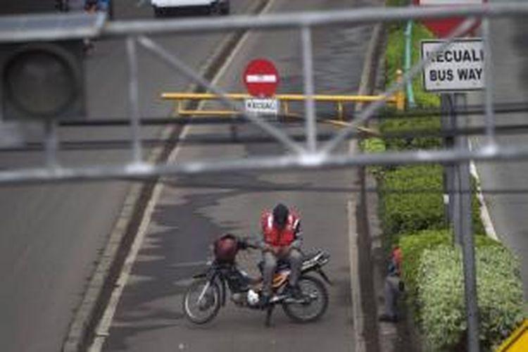 Petugas membuka telepon genggam di atas sepeda motor yang digunakan untuk menutup jalur bus Transjakarta di Jalan Otto Iskandardinata, Jakarta Timur, Rabu (29/5/2013). Jalur tersebut ditutup karena ada bus transjakarta yang mogok.