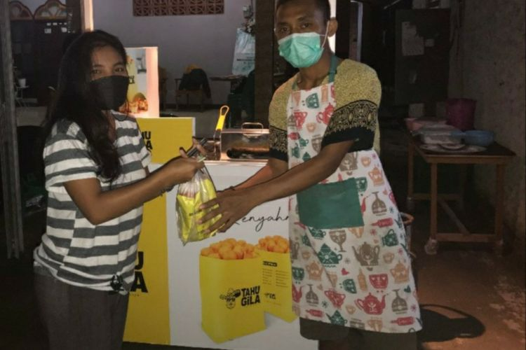 Maksimilianus Dodi Rau (kanan) sedang berpose dengan seorang pembeli Tahu Gila Waingapu, Sabtu (15/5/2021) malam.