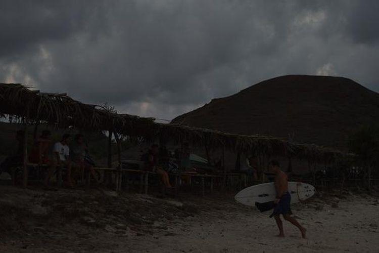 Seorang wisatawan mancanegara berjalan di pasir usai berselancar di Pantai Seger, Desa Kuta, Kecamatan Pujut, Lombok Tengah, Nusa Tenggara Barat, Jumat (20/11/2015) sore. Pantai Seger merupakan tempat berselancar bagi wisatawan yang telah memiliki keahlian.