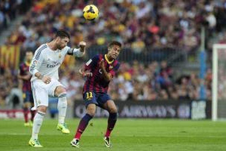 Bek Real Madrid Sergio Ramos (kiri) berebut bola dengan striker Barcelona Neymar da Silva Santos Junior dalam el Clasico di Camp Nou, Sabtu (26/10/2013).