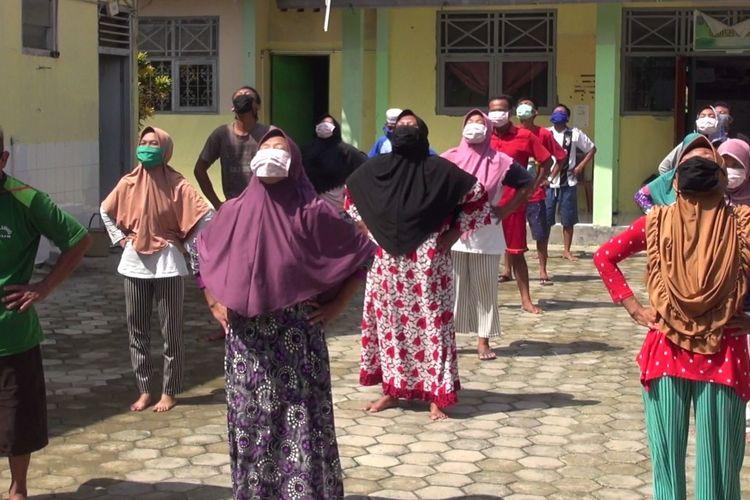 Sejumlah pekerja pabrik kecap berstatus ODP yang diisolasi komunal berolahraga sambil berjemur di halaman gedung bekas puskesmas di Desa Penusupan, Kecamatan Pangkah, Kabupaten Tegal, Jawa Tengah, Kamis (16/4/2020)