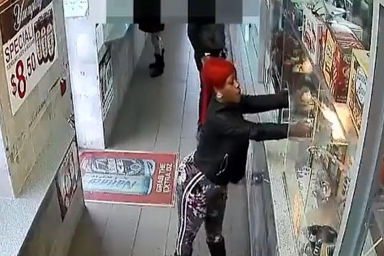 Potongan rekaman kamera pengawas menunjukkan perempuan berambut merah yang menyemprotkan obor api ke kasir sebuah kedai.