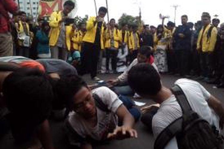 Aksi teatrikal yang menggambarkan penurunan harga BBM kembali oleh mahasiswa di depan Istana Merdeka, Rabu (19/11/2014).