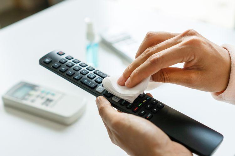 Ilustrasi membersihkan remote TV.