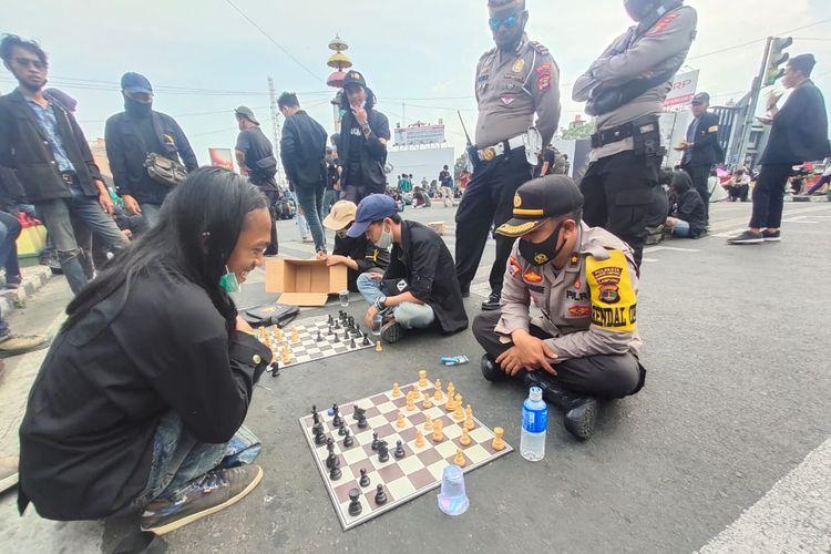Peserta demonstrasi menolak omnibus law di Lampung menantang aparat kepolisian bermain catur, Rabu (14/10/2020) siang.