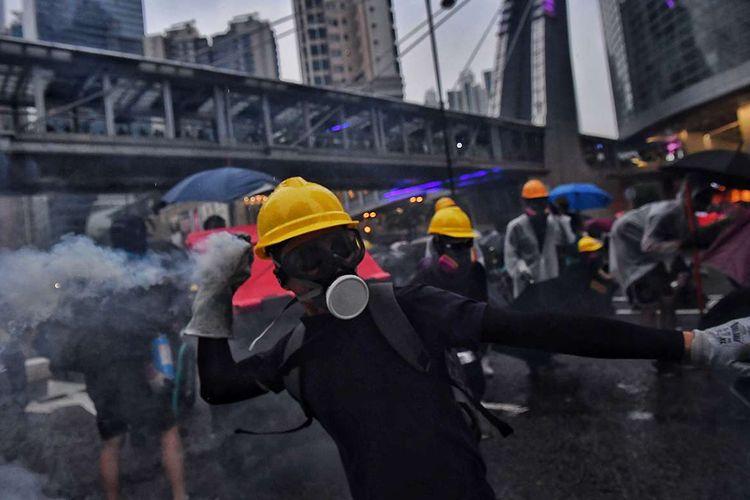 Pengunjuk rasa pro-demokrasi berusaha melempar balik gas air mata ke arah polisi, saat terjadi bentrokan di Tseun Wan, Hong Kong, Minggu (25/8/2019). Aksi protes telah bergulir selama 3 bulan terakhir di Hong Kong, dimulai ketika Kepala Eksekutif Hong Kong Carrie Lam memperkenalkan undang-undang yang bisa mengekstradisi kriminal ke China daratan.