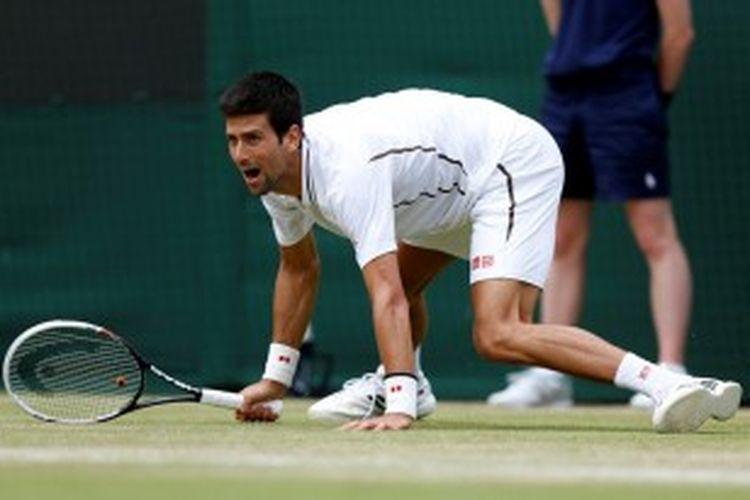 Petenis Serbia, Novak Djokovic terpeleset setelah mengembalikan bola Tomas Berdych dari Ceko, saat bertemu di babak perempat final turnamen Grand Slam Wimbledon, Rabu (3/7/2013).