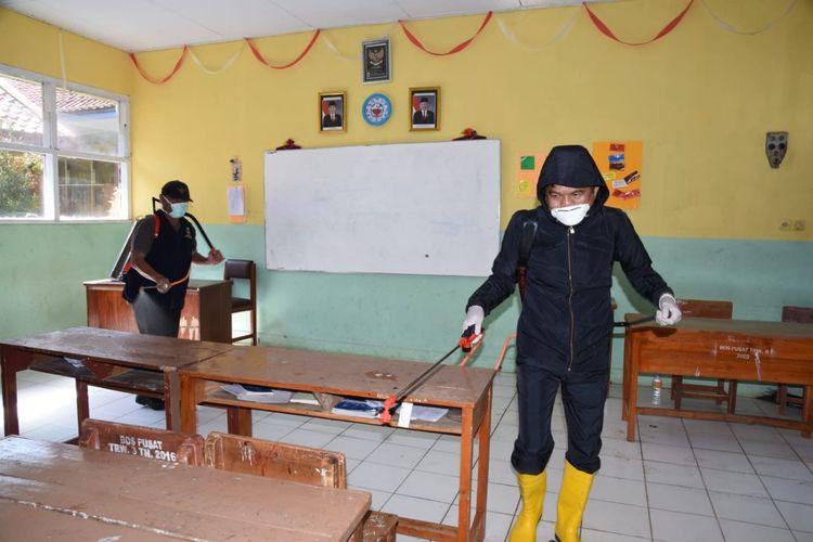 Anggota DPR RI Dedi Mulyadi (kanan) ikut membantu menyemprot ruangan sekolah dengan disinfektan di Purwakarta, Selasa (17/3/2020).