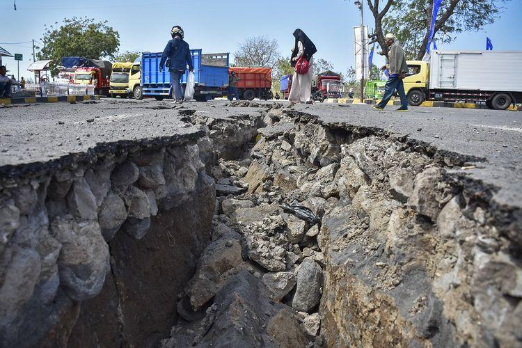 Sejumlah orang melintas di areal parkir ruang tunggu yang retak akibat gempa, di Pelabuhan Kayangan, Lombok Timur, NTB, Senin (20/8). Retakan areal parkir sedalam sekitar 1 meter tersebut akibat gempa bumi yang berkekuatan 7 Skala Richter yang mengguncang Lombok pada Minggu malam pukul 22.56 Wita.