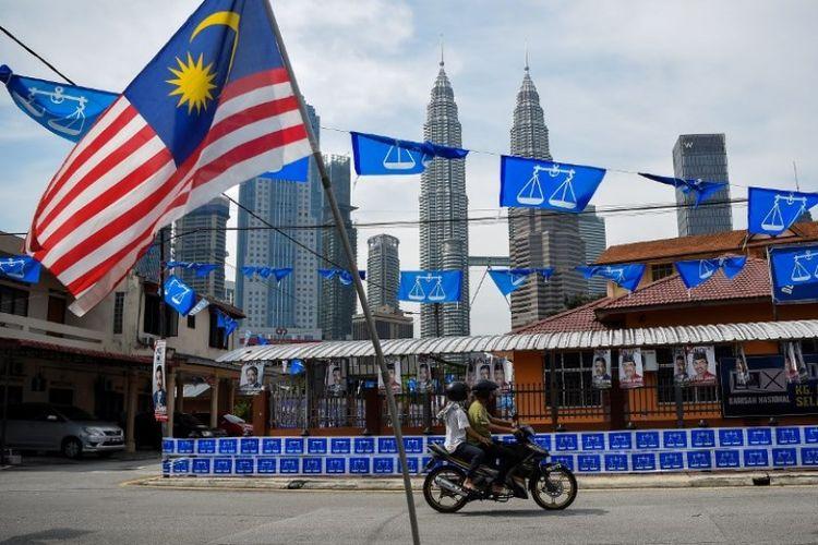 Bendera Malaysia berkibar dengan latar belakang pemandangan menara kembar Petronas dan bendera kecil dari partai Barisan Nasional. (AFP/Manan Vatsyayana)