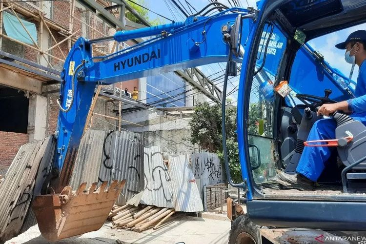 Petugas merobohkan pagar penutup di lokasi berdirinya bangunan tanpa IMB di Cawang, Jakarta, Kamis (8/4/2021).