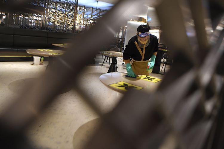 Petugas kebersihan membersihkan meja di Mal Senayan City, Jakarta, Senin (14/9/2020). Pada masa pembatasan sosial berskala besar (PSBB) jilid II atau PSBB pengetatan yang mulai diterapkan 14 September ini oleh Pemprov DKI Jakarta, mal atau pusat perbelanjaan tetap diizinkan beroperasi dengan kapasitas wajib maksimal 50 persen dari kapasitas bersangkutan.