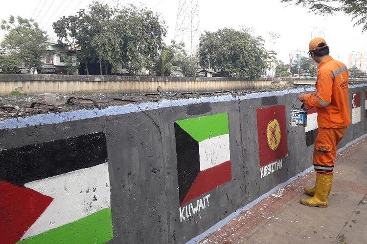 Petugas Penanganan Prasarana dan Sarana Umum (PPSU) Rawa Buaya membuat mural di tembok jalan pembatas Kali Mookervart, Jakarta Barat pada Senin (30/7/2018).