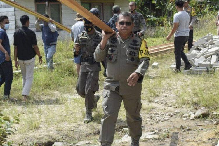 Kapolda Sulteng Irjen Pol Abdul Rakhman Baso mengangkat kayu yang akan digunakan untuk membangun kembali rumah yang bakar oleh terduga teroris kelompok Mujadin Indonesia Timur (MIT) Poso, dalam kejadian kekerasan di Kabupaten Sigi, Jumat (27/11/2020) lalu, di Sigi, Kamis (3/12/2020).