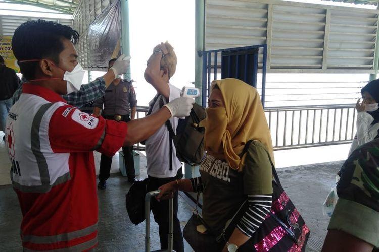 Tim gabungan dari Dinas Kesehatan Nunukan dan Satuan Tugas Pengamanan Perbatasan Yonif Raider 600 Modang saat memeriksa suhu tubuh WNI yang melintas melalui pintu keluar masuk Nunukan di Pelabuhan Liem Hu Djung, Selasa (31/3/2020).