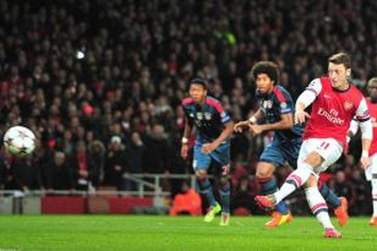 Gelandang Arsenal, Mesut Oezil, saat mengeksekusi tendangan penalti pada leg pertama babak 16 besar Liga Champions melawan Bayern Muenchen, Rabu (19/2/2014).