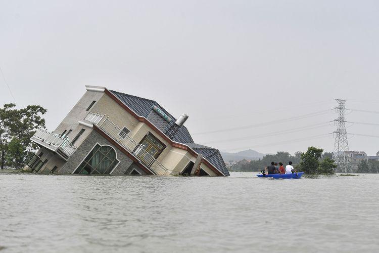 Foto tertanggal 15 Juli 2020 memperlihatkan penduduk mengendarai perahu saat melewati rumah yang hanyut diterjang banjir, di dekat Danau Poyang. Banjir melanda akibat hujan deras yang mengguyur Poyang, Kota Shangrao, Provinsi Jiangxi, China.