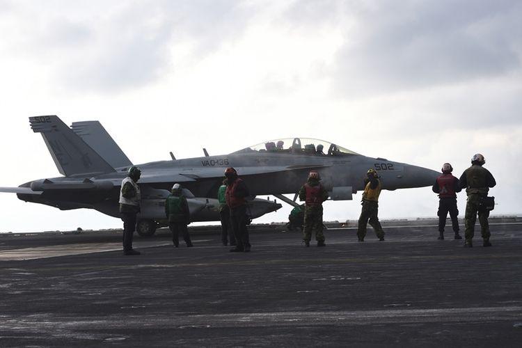 Anggota kru Angkatan Laut AS berdiri di depan pesawat tempur di dek kapal induk Nimitz USS Carl Vinson selama latihan militer gabungan Korea Selatan-AS di laut timur Semenanjung Korea pada 14 Maret 2017. )(AFP/Jung Yeon Je)