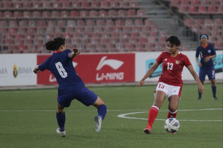 Pemain timnas putri Indonesia Safira Ika Putri (kanan) mencoba melewati adangan pemain Singapura Danelle pada laga lanjutan Kualifikasi Piala Asia Wanita 2022, Senin (27/9/2021).