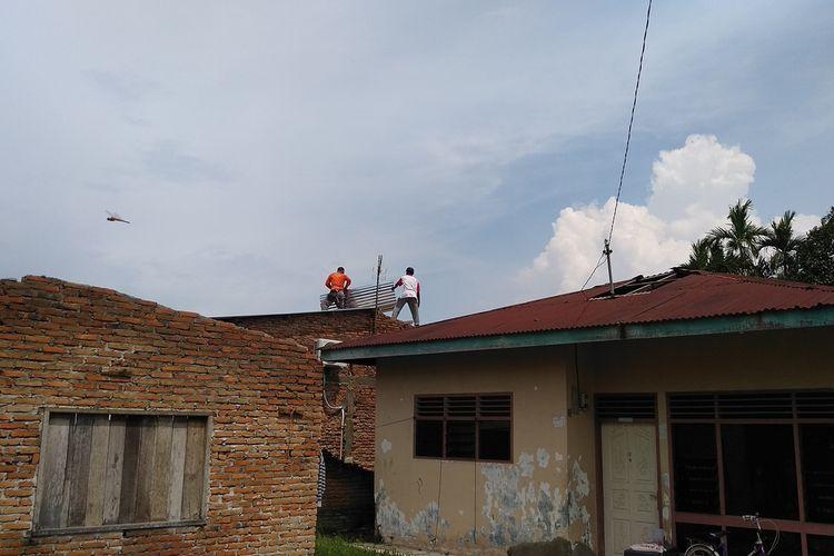 Petugas BPBD membantu warga memperbaiki kerusakan di rumah yang rusak akibat bencana angin puting beliung di Desa Amplas/Tambak Rejo, Kecamatan Percut Sei Tuan, Deli Serdang pada Rabu (7/4/2021) sore.