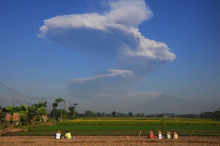 Sejumlah petani melihat kepulan asap letusan freatik Gunung Merapi di Sawit, Boyolali, Jawa Tengah, Jumat (11/5/2018). Berdasarkan data Badan Nasional Penanggulangan Bencana (BNPB) terjadi letusan freatik Gunung Merapi disertai suara gemuruh dengan tekanan sedang hingga kuat dan tinggi kolom 5.500 meter dari puncak kawah pada pukul 07.32 WIB.
