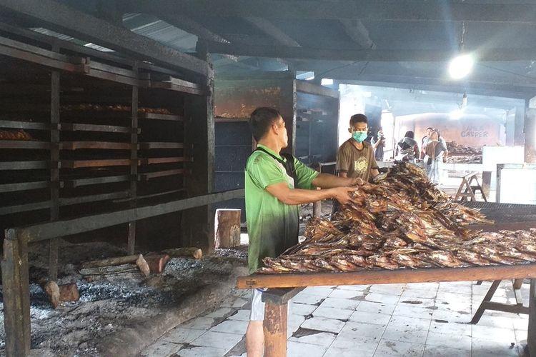 Pekerja di sentra pengolahan ikan patin sedang menyortir ikan yang sudah diasap sebelum dipacking di Desa Koto Masjid, Kecamatan XIII Koto Kampar, Kabupaten Kampar, Riau, Kamis (7/1/2021).