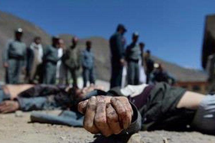 Pasukan keamanan Afganistan berjaga di dekat jasad anggota kelompok militan yang menyerang distrik Bazarak, Provinsi Panjshir, Afganistan, Rabu (29/5/2013). Bersamaan dengan serangan ini, kelompok militan juga menyerang sebuah kantor palang merah internasional di Jalalabad.