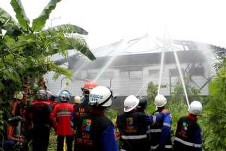 Petugas pemadam kebakaran memandamkan api di lingkungan perusahaan alat berat di Samarinda, Sabtu (8/10/2016).