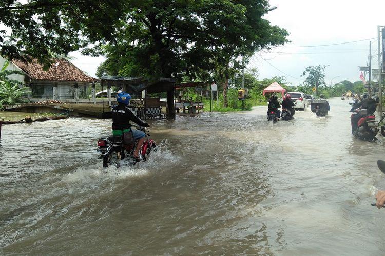 Air luapan anak Kali Lamong yang masih merendam sebagian Jalan Raya Benjeng, Gresik, Senin (14/12/2020).