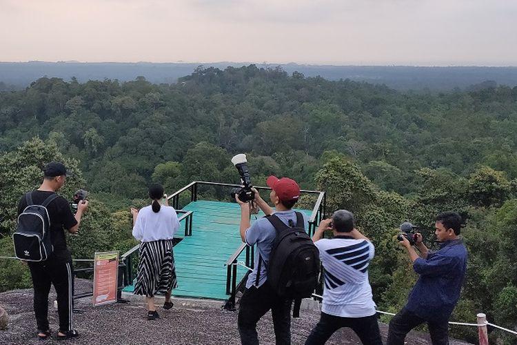 Pengunjung menikmati dan mencoba spot foto di Puncak Bukit Peramun, Belitung, Sabtu (9/11/2019).