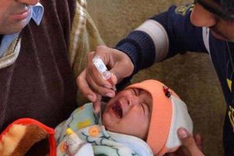 Seorang sukarelawan memberikan vaksin polio kepada seorang bayi di Peshawar, Pakistan. Pakistan bersama Afganistan dan Nigeria menjadi medan tempur terakhir pemberantasan polio di dunia.