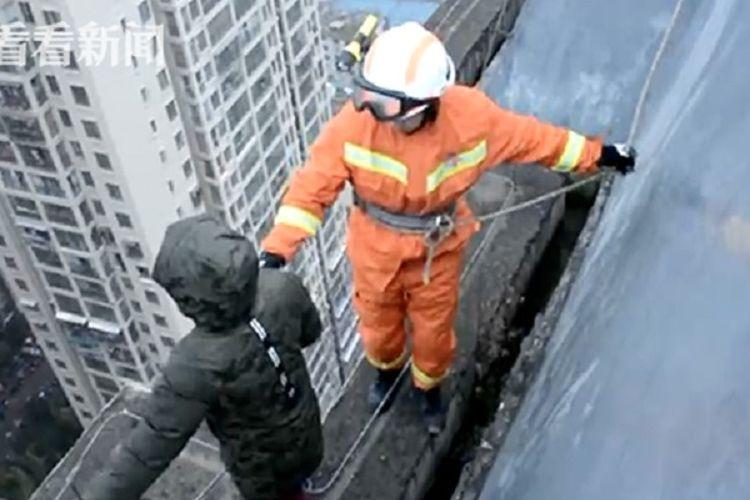 Gambar memperlihatkan petugas pemadam kebakaran di Bijie, China, berusaha membujuk bocah berusia delapan tahun yang berniat bunuh diri dari lantai 33 karena tak mau sekolah.
