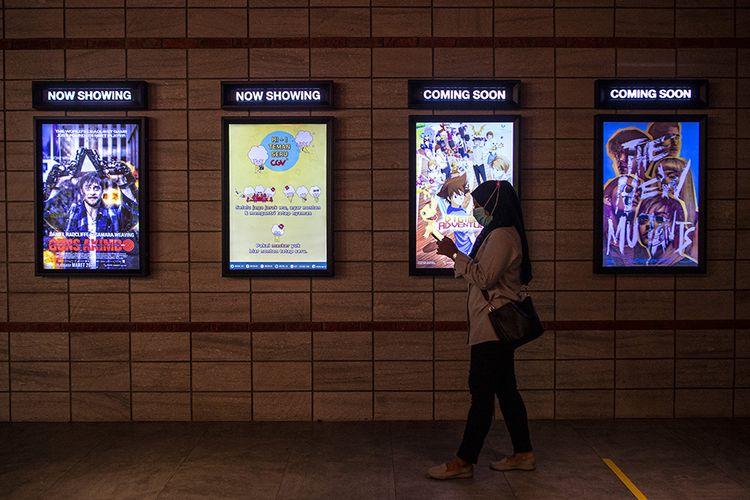Pengunjung melintas di depan jadwal film yang akan diputar di salah satu bioskop di Palembang, Sumatera Selatan, Rabu (4/11/2020). Pemerintah Kota Palembang kembali mengizinkan bioskop kembali beroperasi dengan menerapkan protokol kesehatan Covid-19.