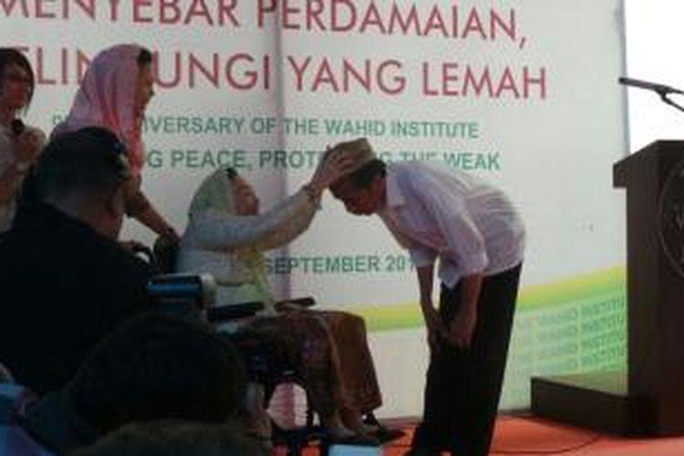 Sinta Nuriyah memberikan sebuah peci milik almarhum suaminya, Abdurrahman Wahid kepada Gubernur DKI Joko Widodo. Pemberian hadiah itu dilakukan usai Jokowi menjadi key note speaker Hari Lahir ke 9 Wahid Institute.